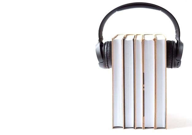 Kopfhörer und bücher auf weißem hintergrund. hörbuchkonzept. Premium Fotos