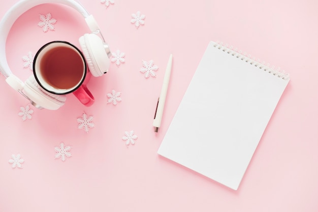 Kopfhörer und getränk nahe schneeflocken und notizblock Kostenlose Fotos