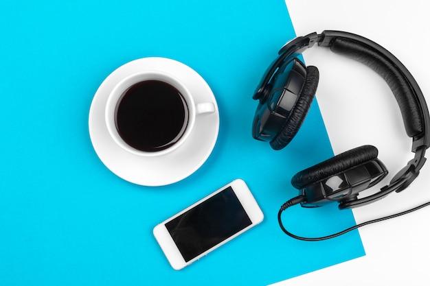 Kopfhörer und kaffeetasse auf blauem hintergrund, draufsicht Premium Fotos