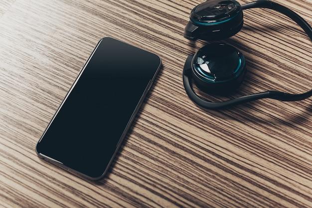 Kopfhörer und smartphone auf holz Premium Fotos