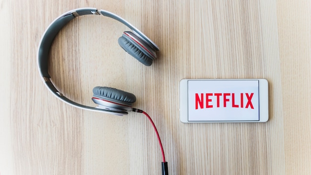 Kopfhörer in der Nähe von Smartphone mit Netflix-Logo Kostenlose Fotos