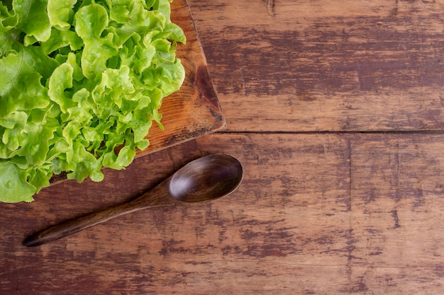Kopfsalat, der auf einen braunen bretterboden gesetzt wird. Kostenlose Fotos