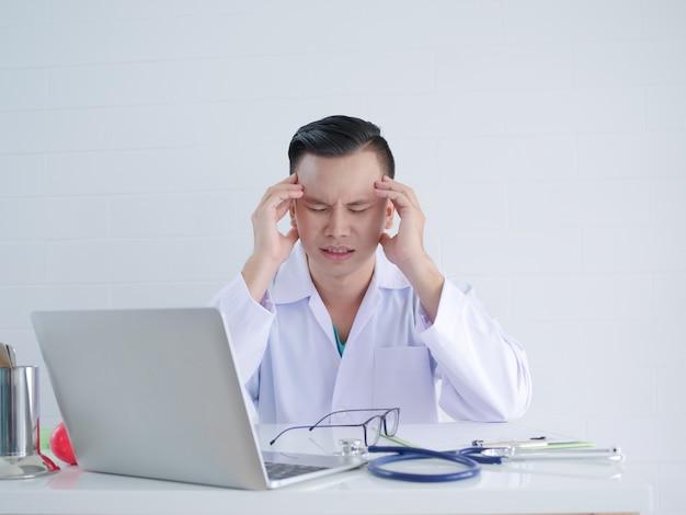 Kopfschmerzen junger doktor während des arbeitens. Premium Fotos
