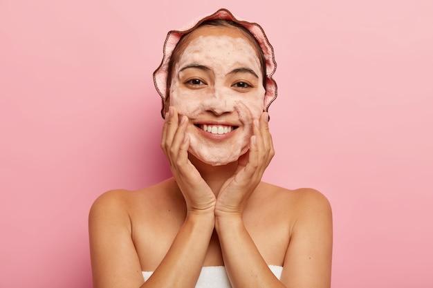 Kopfschuss der jungen koreanischen frau berührt makellose weiche haut, wäscht gesicht mit hygieneseife mit schäumendem reinigungsmittel, eingewickelt in handtuch, hat badekappe auf dem kopf, isoliert auf rosa wand. reinigungskonzept Kostenlose Fotos