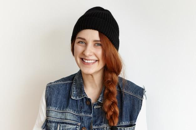 Kopfschuss des schönen weiblichen modells mit blauen augen und niedlichem fröhlichem lächeln, das an der weißen wand aufwirft Kostenlose Fotos