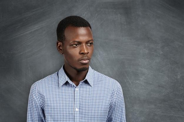 Kopfschuss eines ernsthaften nachdenklichen jungen afrikanischen mathematiklehrers im freizeithemd, der mit nachdenklichem ausdruck beiseite schaut, an der tafel im klassenzimmer steht und auf seine schüler für die nächste lektion wartet Kostenlose Fotos