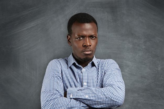 Kopfschuss eines wütenden, ernsthaften afrikanischen lehrers mit verschränkten armen, der mit seinen schlecht benommenen schülern unzufrieden ist und an einer leeren tafel mit kopierraum für ihren text oder werbeinhalt steht Kostenlose Fotos
