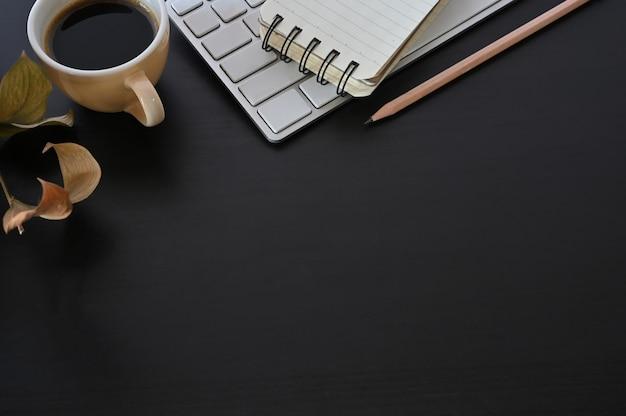 Kopieren sie platz schreibtischkaffee, computertastatur und notizblock mit bleistift auf schwarzer tabelle. Premium Fotos
