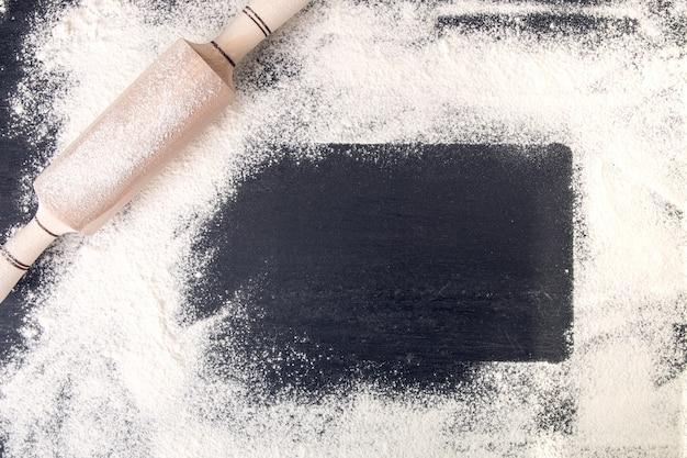 Kopieren sie platz um nudelholz und mehl auf schwarzem hintergrund. Premium Fotos