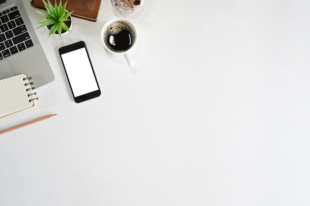 Kopieren sie platz von smartphone, laptop, kaffee, buch und notizblock auf schreibtisch Premium Fotos