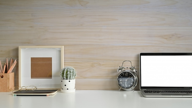 Kopieren sie raumarbeitsplatzmodelllaptop, fotorahmen, wecker und kaktus auf schreibtisch mit hölzerner wand. Premium Fotos