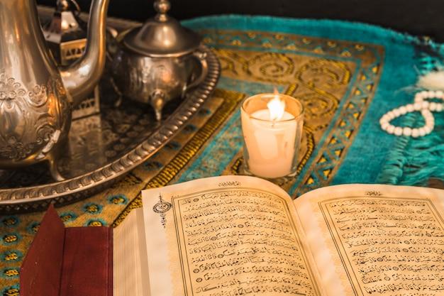 Koran in der nähe von kerze und tablett mit geschirr Kostenlose Fotos