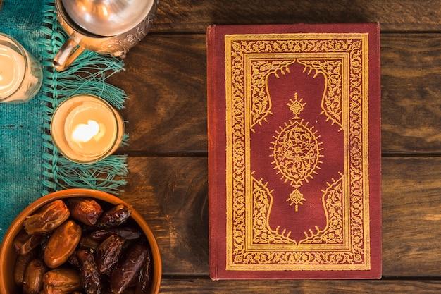 Koran in der nähe von süßen datteln und kerzen Kostenlose Fotos