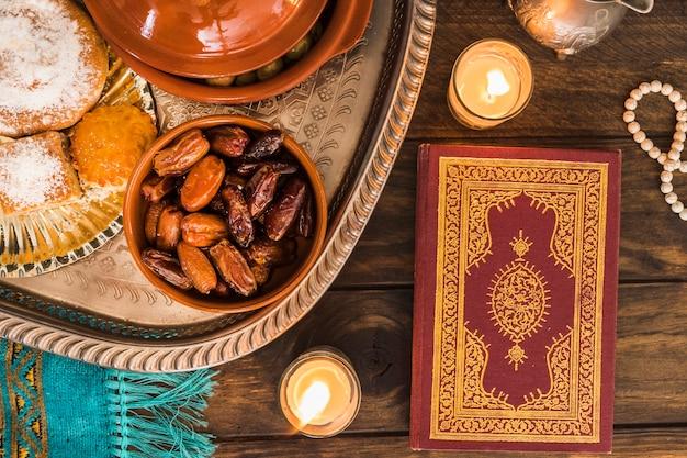Koran und kerzen in der nähe von arabischem essen Kostenlose Fotos