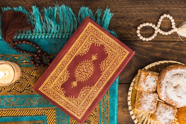 Koran und perlen in der nähe von kerze und gebäck Kostenlose Fotos