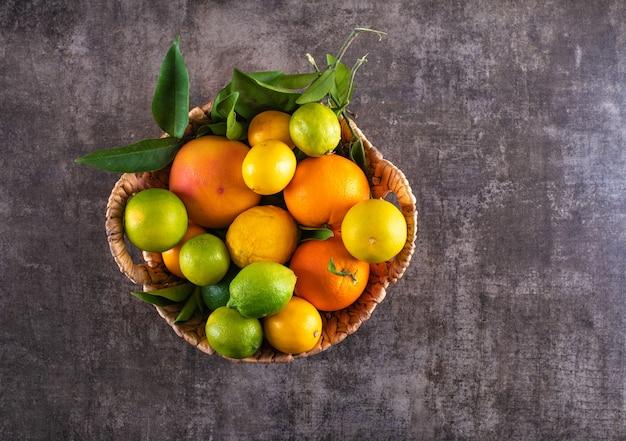 Korb gefüllt mit zitrusfrüchten auf grauer steinoberfläche Kostenlose Fotos