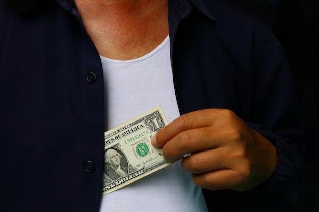 Korruption. mann, der geld in anzugsjacke einsetzt Premium Fotos