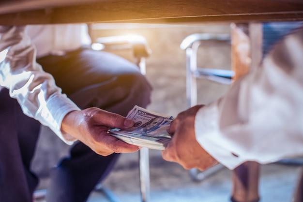 Korruptionskonzept, geschäftsmann, der bestechungsgeld vom mann unter tabelle nimmt Premium Fotos