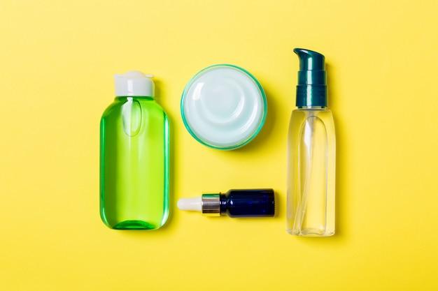 Kosmetik-badekurort-brandingmodell, draufsicht mit kopienraum. satz von rohren und gläser sahne flach lag auf gelbem grund Premium Fotos
