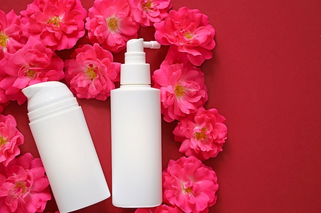 Kosmetik & hautpflege mockup. creme und serum mit rosenextrakt in weißen kosmetikflaschen auf rosa rosen Premium Fotos