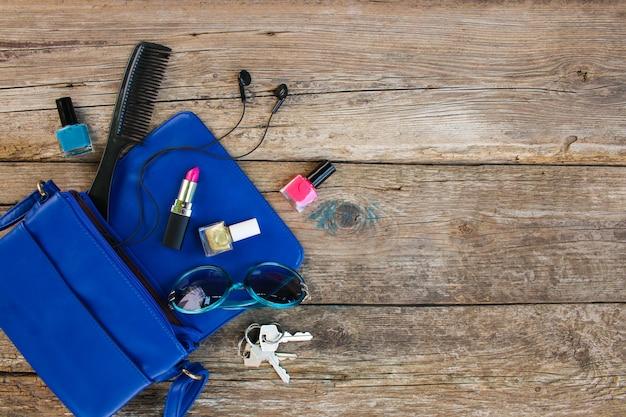 Kosmetik und accessoires für frauen fielen aus der blauen handtasche. ansicht von oben. Premium Fotos