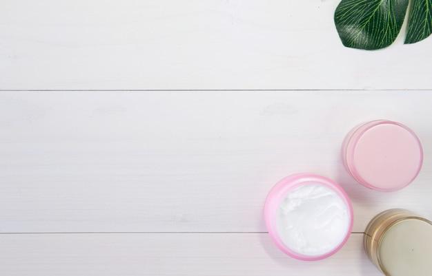 Kosmetik und hautpflegeprodukt und grünblätter auf weißer hölzerner tabelle Premium Fotos