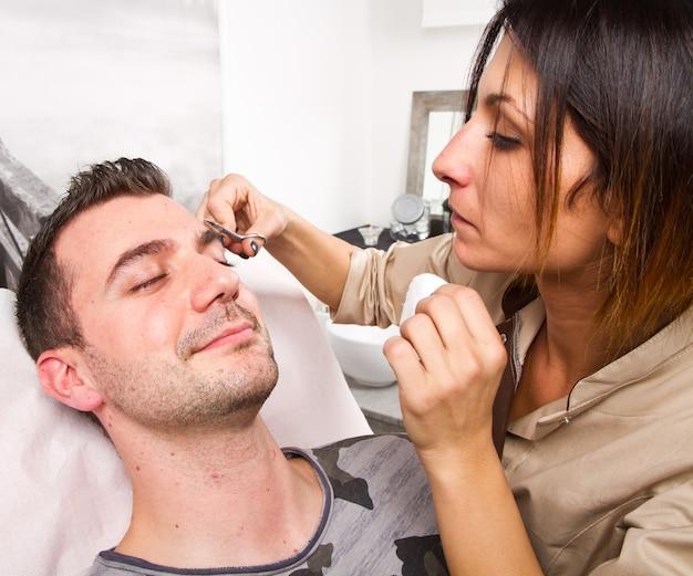Kosmetiker, der augenbrauen eines schönen mannes mit pinzette in einem schönheitssalon zupft Premium Fotos