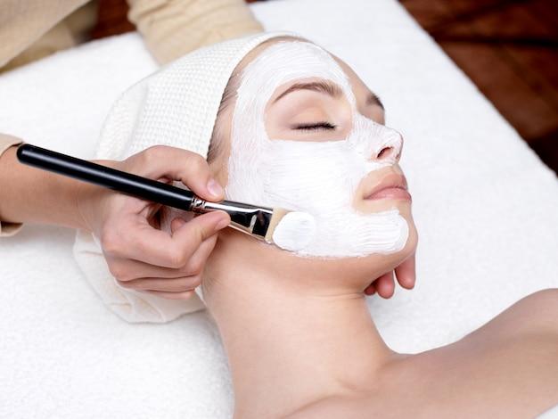 Kosmetiker, der gesichtsschönheitsmaske für junge schöne frau am spa-salon anwendet Kostenlose Fotos