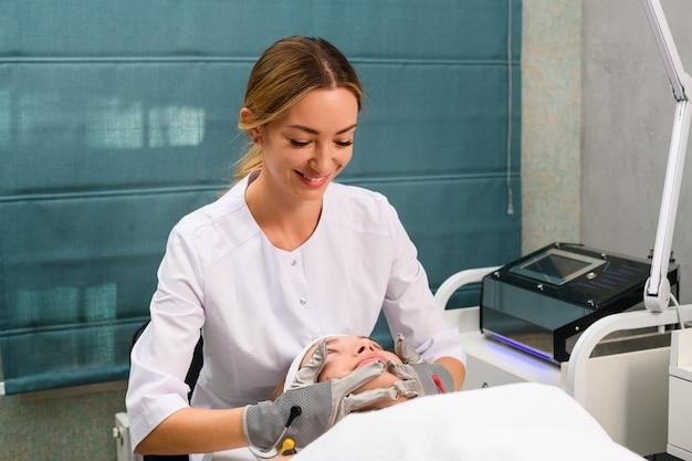 Kosmetiker lächeln während der massage weibliches kundengesicht Premium Fotos