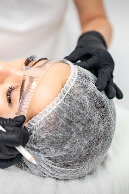 Kosmetikerin, die durch tätowiermaschine permanentes make-up auf augenbrauen aufträgt Premium Fotos