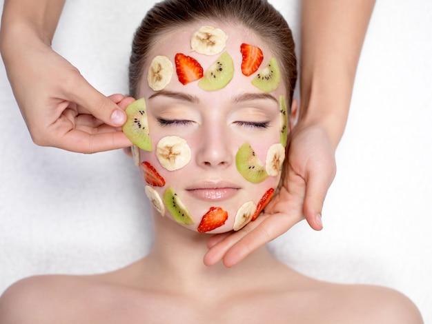 Kosmetikerin, die fruchtmaske auf einem gesicht der schönen jungen frau tut - drinnen Kostenlose Fotos