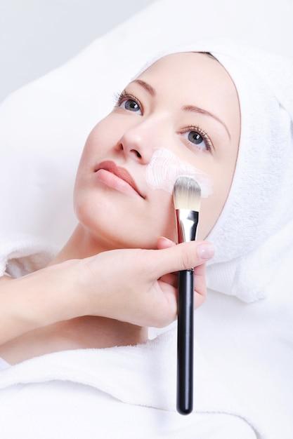 Kosmetikerin, die kosmetische maske im spa-salon für junge frau anwendet Kostenlose Fotos