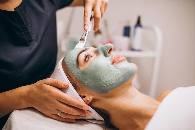Kosmetikerin, die maske auf einem gesicht des kunden in einem schönheitssalon anwendet Kostenlose Fotos