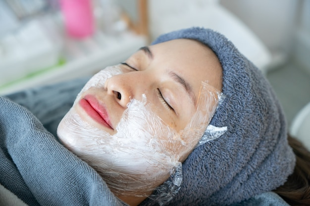 Kosmetikerin, die vor laser oder injektionen anästhesiecreme auf das gesicht der frau aufträgt. Premium Fotos