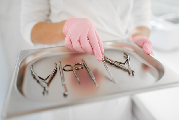 Kosmetikerin hält metallschale mit ausrüstung Premium Fotos