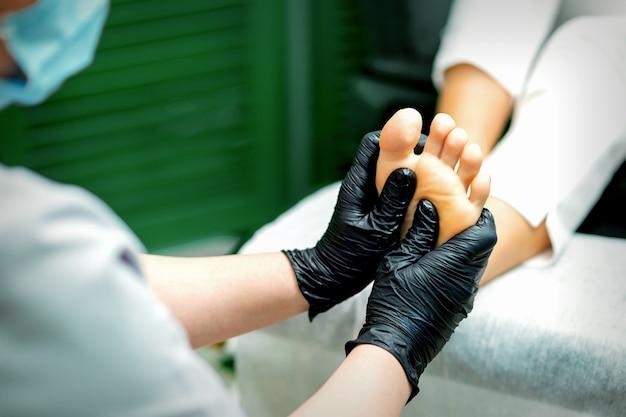 Kosmetikerin in schützenden gummihandschuhen, die massage auf der sohle des weiblichen fußes in einem spa-schönheitssalon tun Premium Fotos