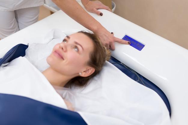 Kosmetikerin startet hydromassage im spa. professionelle moderne kosmetologie. körperpflege. der prozess des hydromassagebades in der kosmetikklinik. Premium Fotos