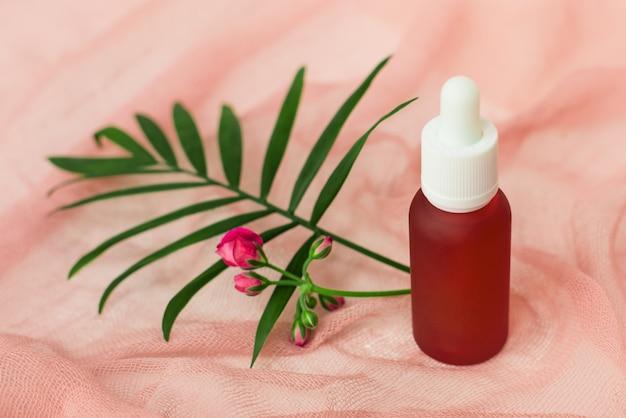 Kosmetikflaschen, rosa ölkrüge und palmblatt Premium Fotos