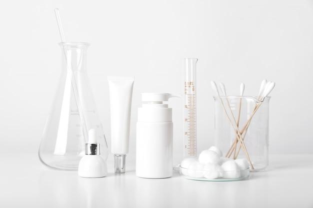 Kosmetikflaschenbehälter und wissenschaftliche glaswaren, blankopaket für das branding, pharmazeutische hautpflege durch den hautarzt, forschung und entwicklung eines schönheitsproduktkonzepts. Premium Fotos