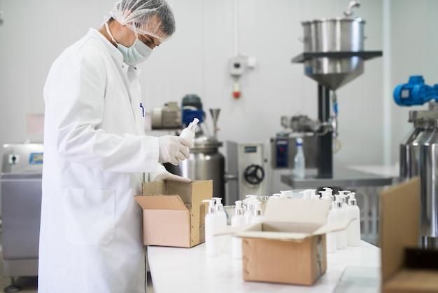 Kosmetikgewebearbeiter, der eine flüssigseife aus einer reihe nimmt und für den transport in eine papierbox legt Premium Fotos
