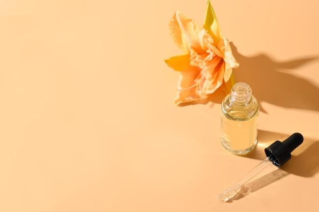 Kosmetiköl oder essenz in glasflasche mit frischen lilienblumen auf beigem raum Premium Fotos