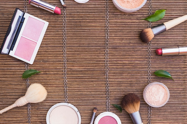 Kosmetikprodukte angeordnet in kreisform auf tischset Kostenlose Fotos