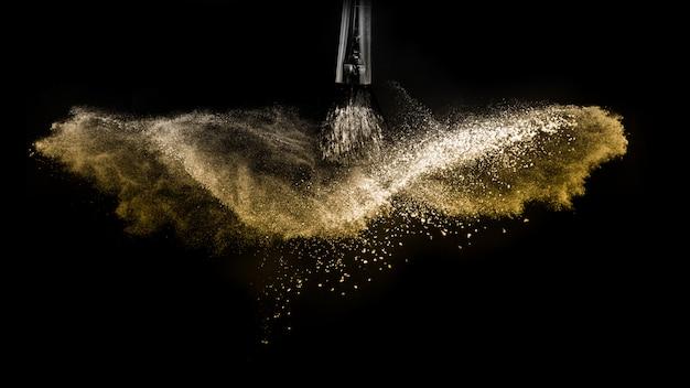 Kosmetische bürste mit dem goldenen kosmetischen puder, das für maskenbildner verbreitet Premium Fotos