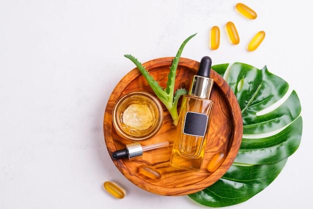 Kosmetische flasche mit öl oder hyaluronsäure und glas mit gesichtsmaske, omega-3-gel-kapseln auf holzplatte, aloe vera und palmblatt und einem weißen tuch Premium Fotos