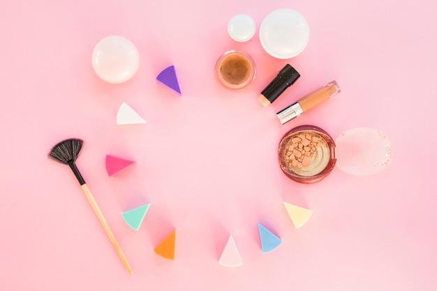 Kosmetische schwämme von verschiedenen farben mit make-up-produkten auf rosa hintergrund Kostenlose Fotos