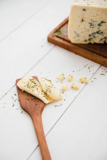 Kräuter mit käse auf spachtel über dem weißen hölzernen schreibtisch Kostenlose Fotos