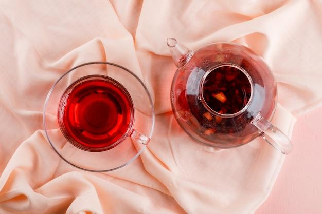 Kräutertee in glasbecher und teekanne auf rosa und textil. Kostenlose Fotos