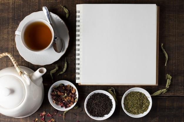 Kräutertee mit teekanne und leerem gewundenem notizbuch auf holztisch Kostenlose Fotos