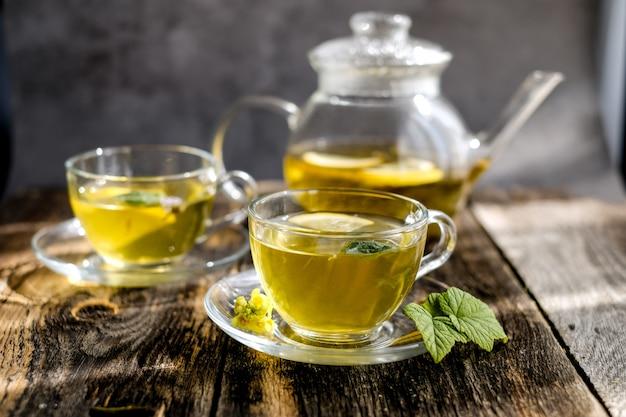 Kräutertee mit zitrone und honig in der glasschale und in der teekanne Premium Fotos