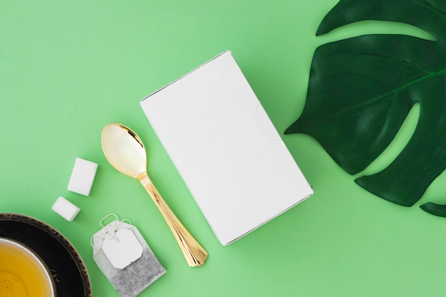 Kräutertee mit zuckerwürfel, teebeutel, löffel, blatt und kasten auf grünem hintergrund Kostenlose Fotos